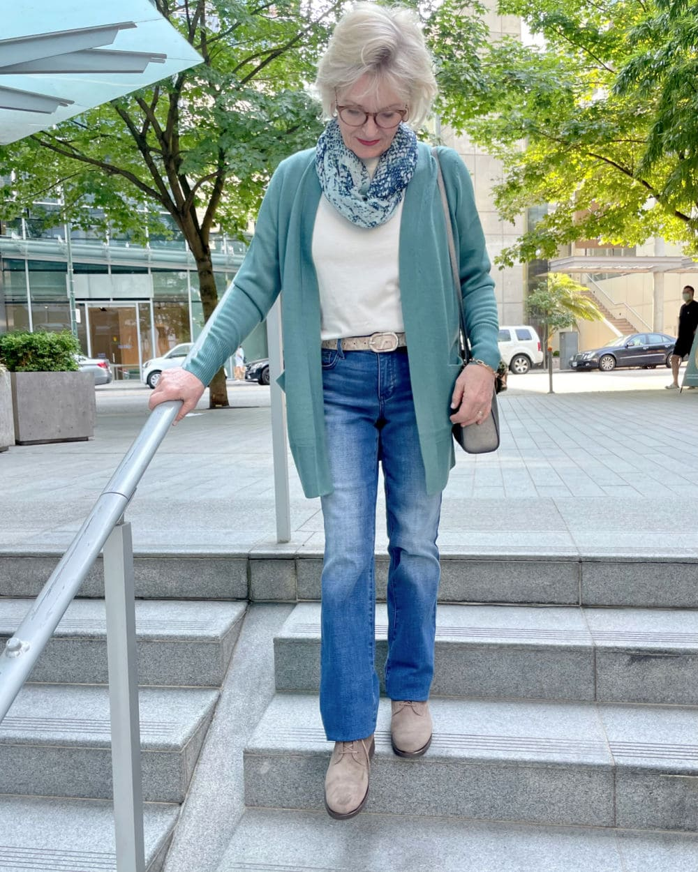 woman walking down stairs wearing teal sweater and nydj jeans from the Nsale