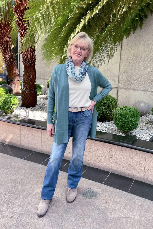over 50 blogger wearing nordstrom sweater in teal over denim