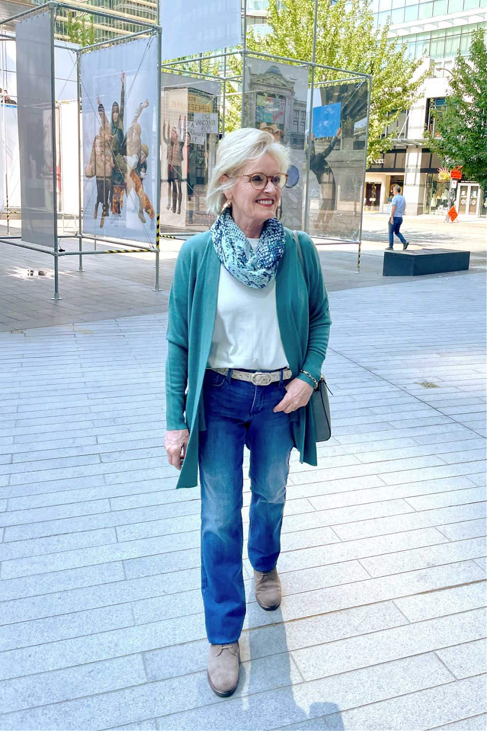 over 50 blogger jennifer connolly wearing nydj and teal cardigan while walking down the sidewalk