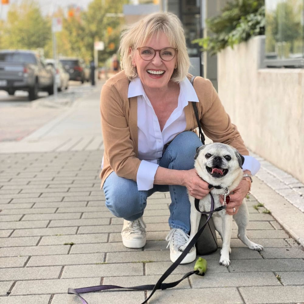 woman bendiong down to hold pug on sidewalk