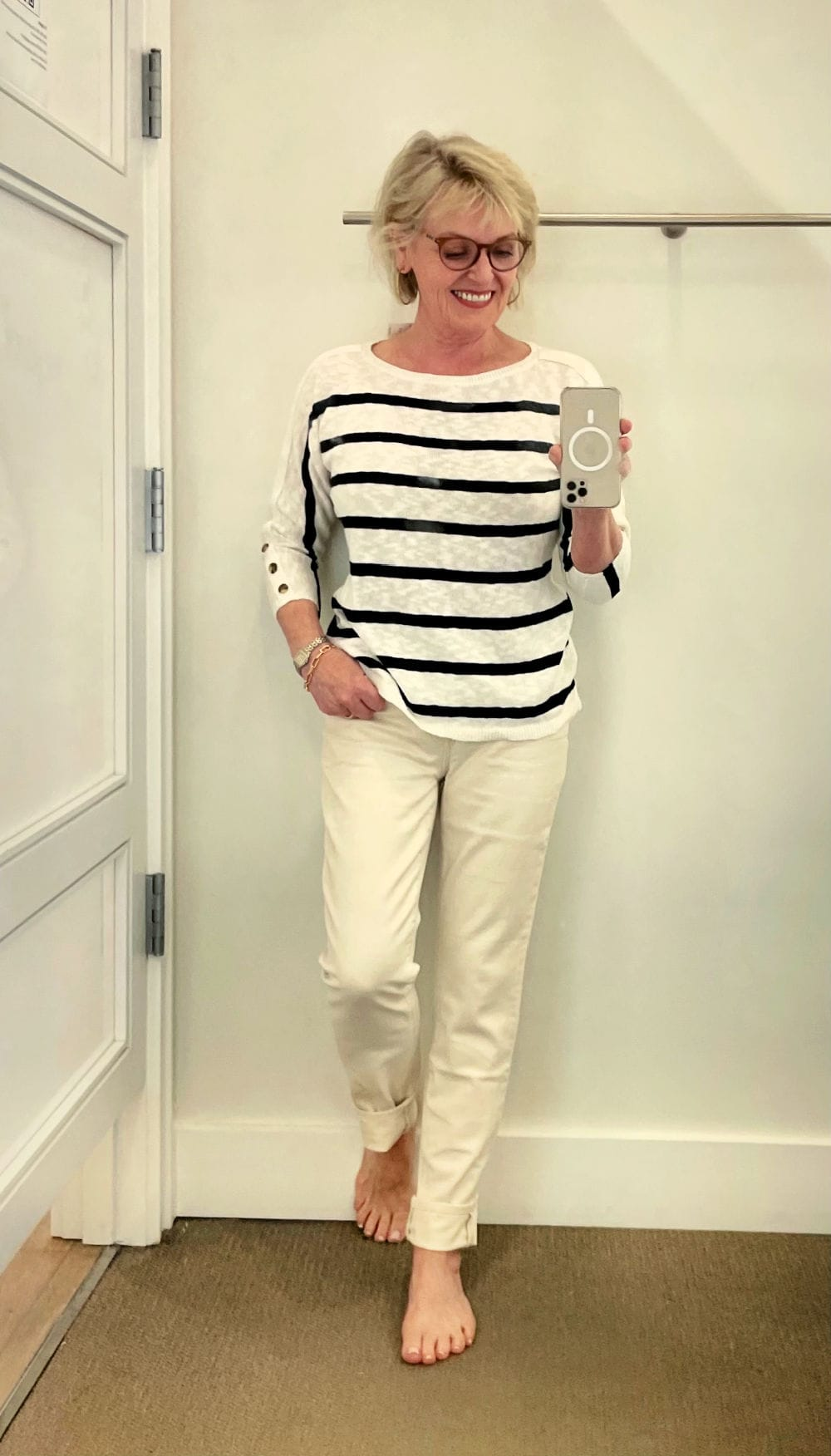 woman wearing stripe sweater and cream jeans