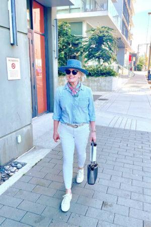woman walking down sidewalk weaing white jeans, chambray shirt, ands denim hat