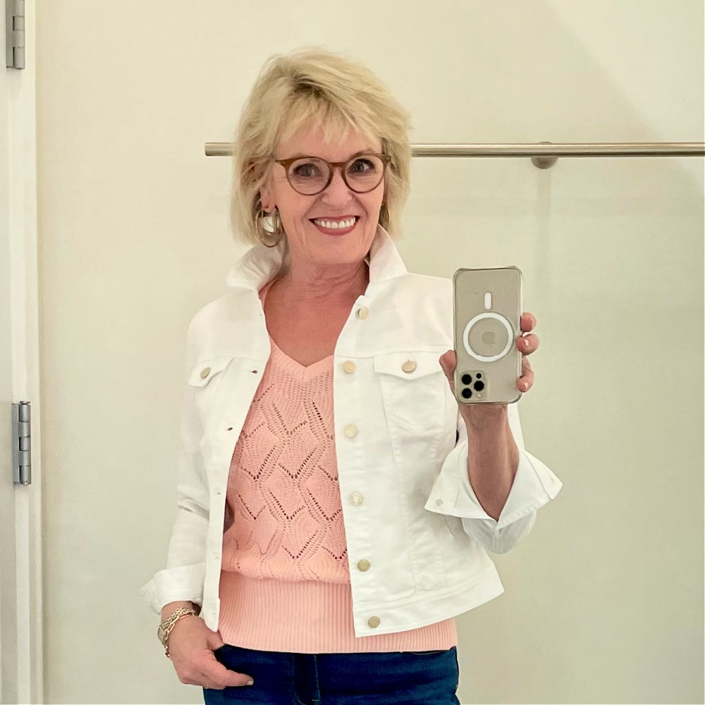 woman takign selfie wearing white denim jacket from Talbots