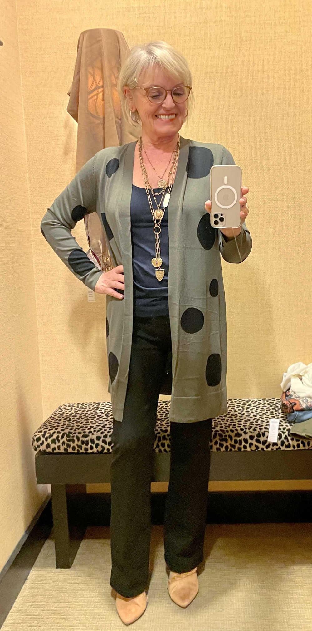 blonde woman wearing green and black polka dot cardigan in chico's store