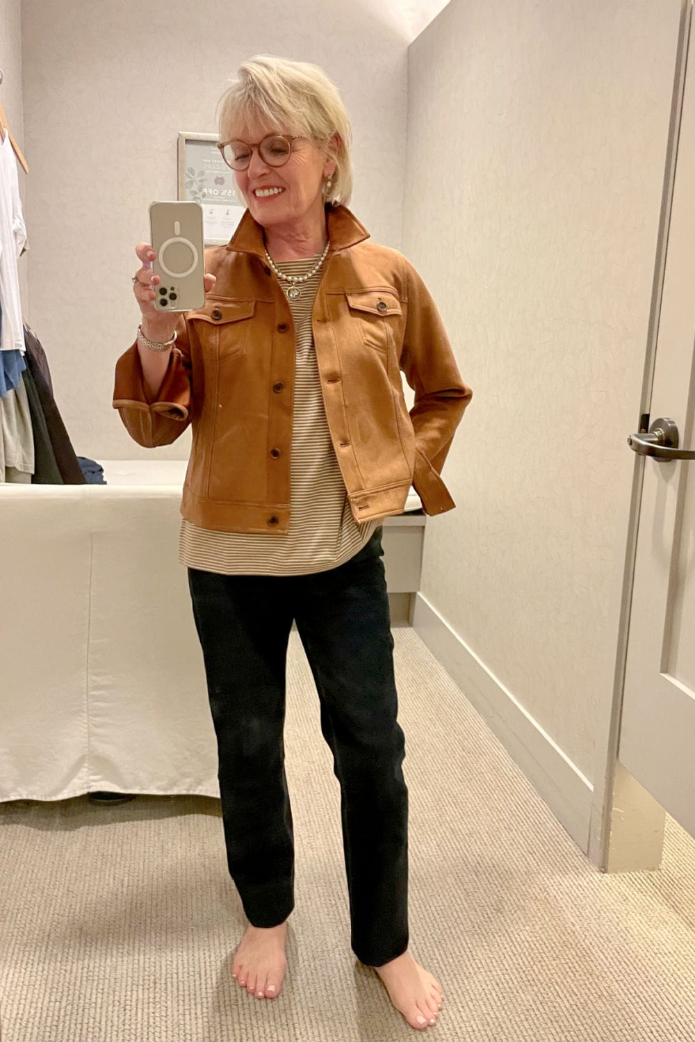 WOMAN WEARING FAUX SUEDE JACKET OVER STRIPED TEE AND JEANS
