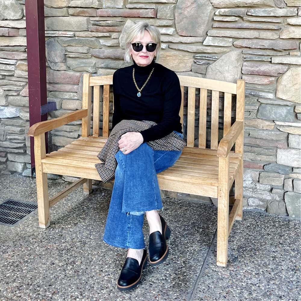 woman sitting on bench wearing modern loafer trend