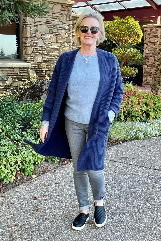 woman walking wearing target long blue sweater grey jeans and black sneakers
