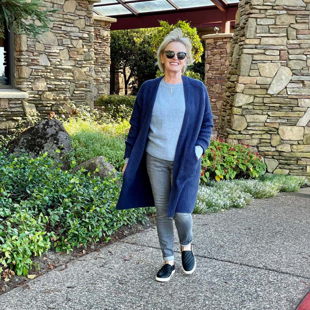 blonde woman walking wearing budget friendly long blue cardigan over blue sweater and gray jeans