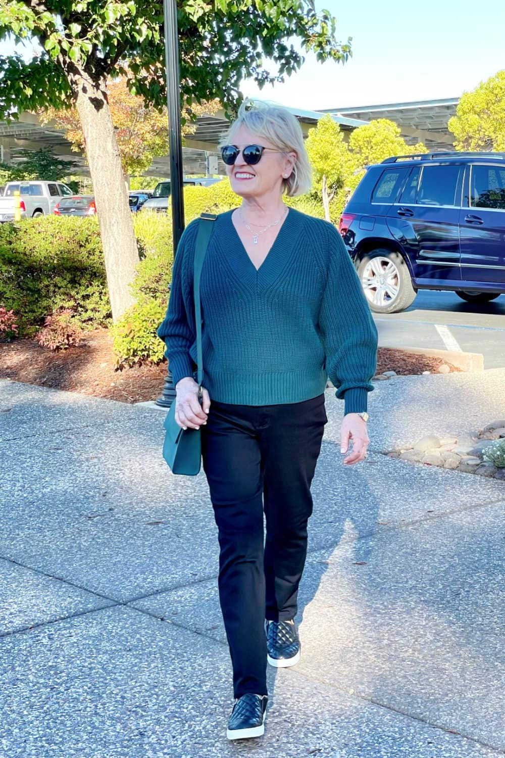 woman in green sweater and black jeans