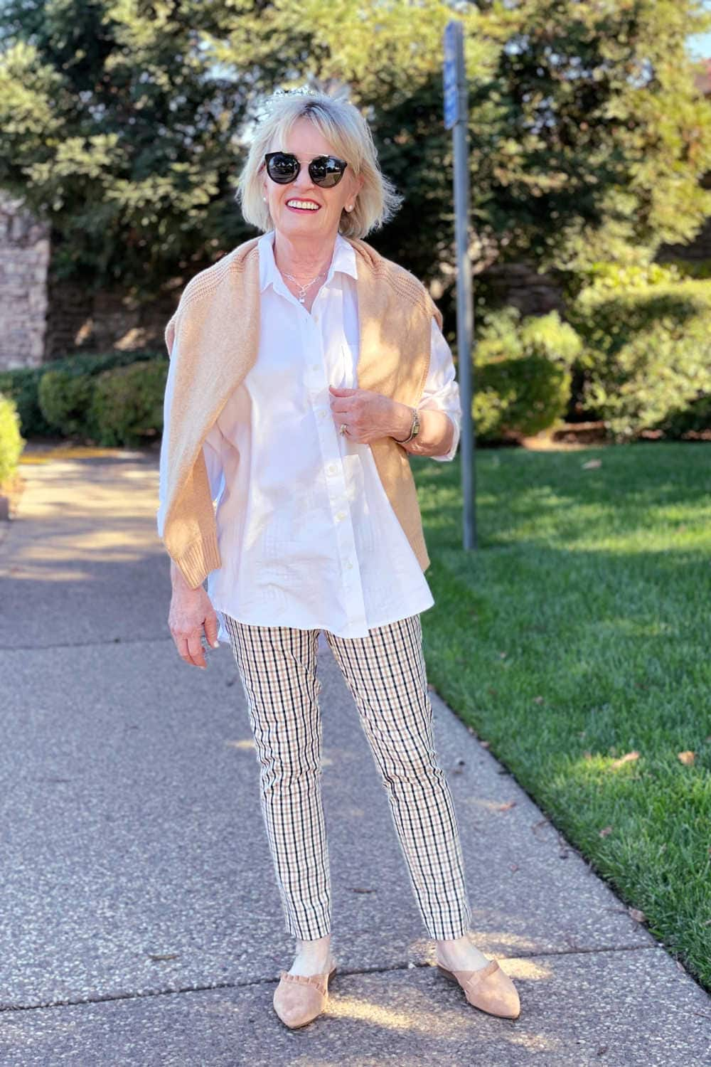 woman wearing white tunic shirt, plaid pants and camel colored slides