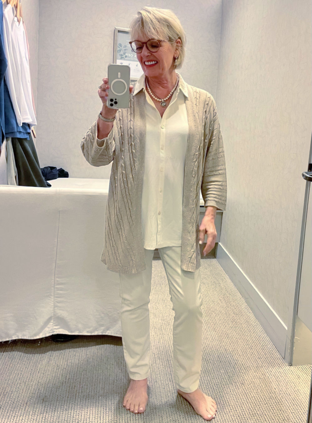 WOMAN WEARING CABLE SWEATER OVER LONG BLOUSE AND IVORY COLORED JEANS AT J JILL