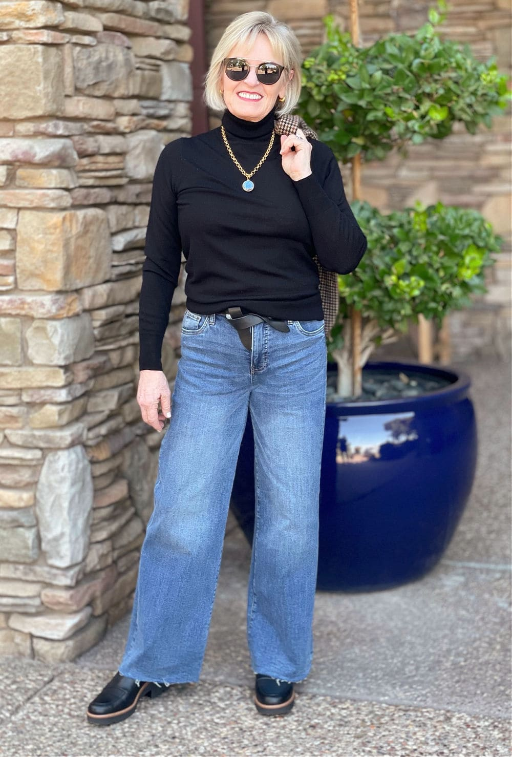 over 50 fashion blogger wearing black turtleneck and wide leg jeans