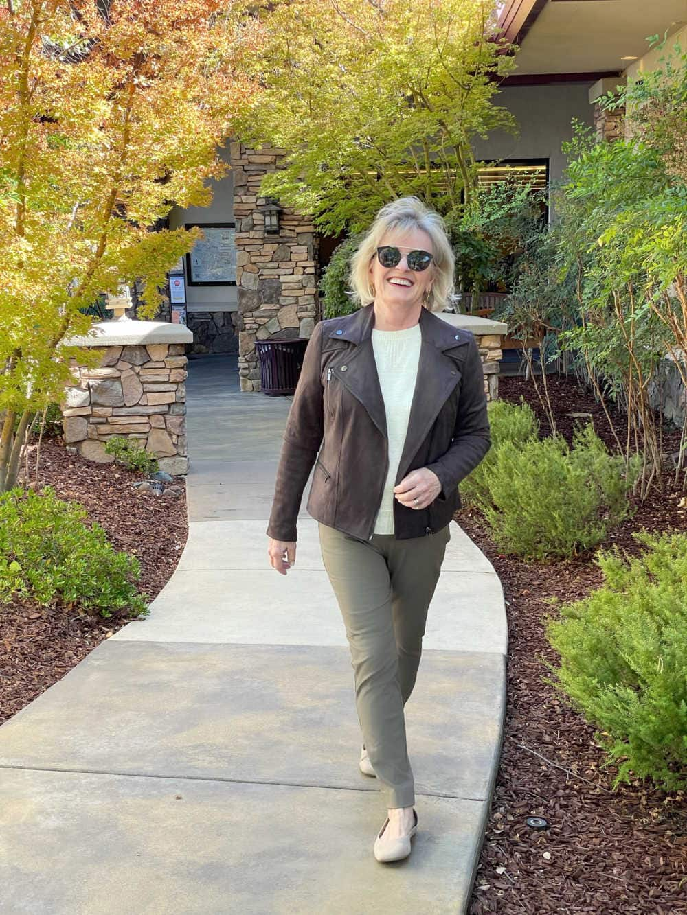 blonde woman walking wearing brown faux suede moto jacket outfit