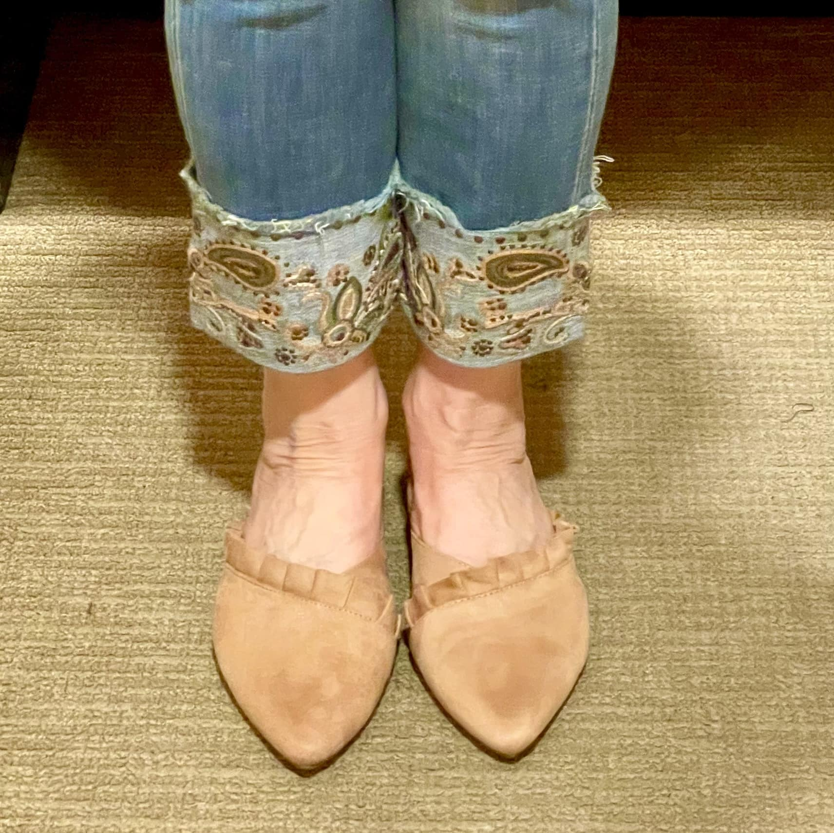 close up of ruffled mule and embroidered jeans cuff