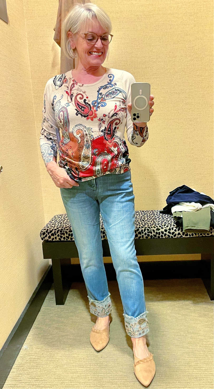 woman wearing print sweater and jeans with embroidered cuffs in chico's dressing room