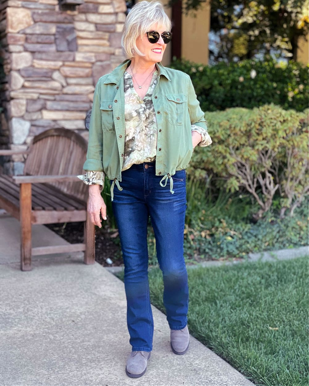 over 50 blogger jennifer connolly of a well stylesd life wearing loghtweight fall outfit of green utility jacket, soft blouse and jeans