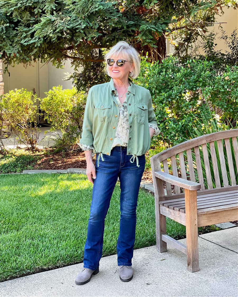 woman wearing blue jeans, suede boots, green jacket and floral shirt for warmer fall days