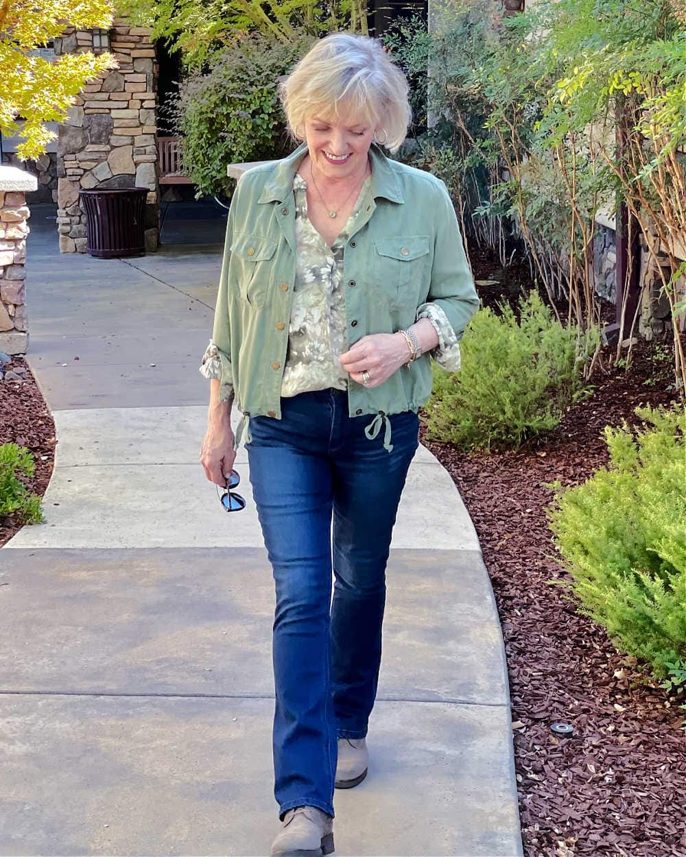 blond woman walking in itty bitty bootcut jeans and green jacket
