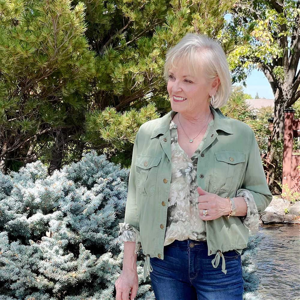 BLONDE WOMAN WEARING FLORAL SHIRT AND GREEN ULTILITY JACKET FOR WARM FALL TEMP