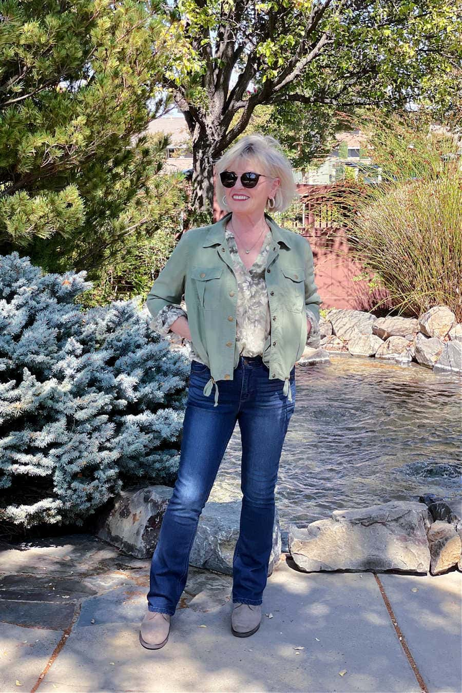over 50 blogger wearing floral blouse, green jacket and jeans from Nordstrom