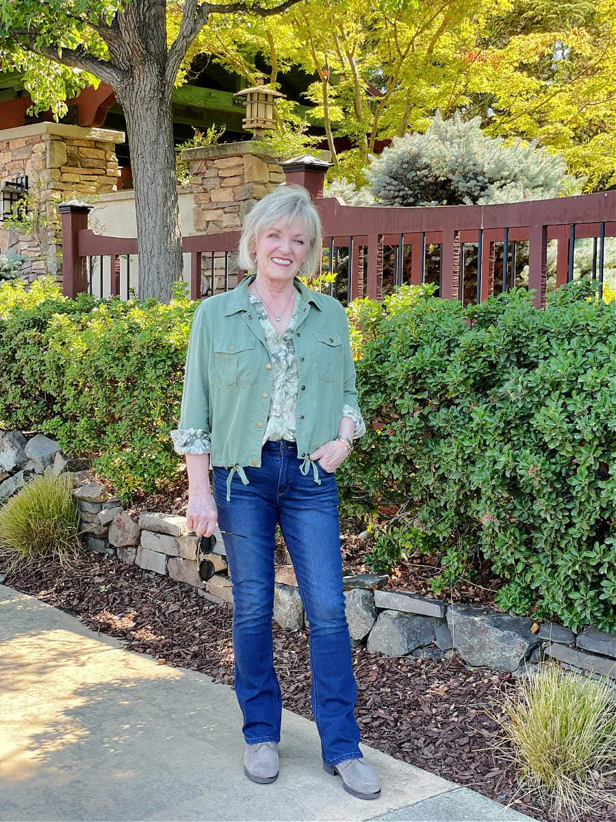 woman wearing floral blouse and lightweight fall utility jacket with jeans and booties standing in front of fence