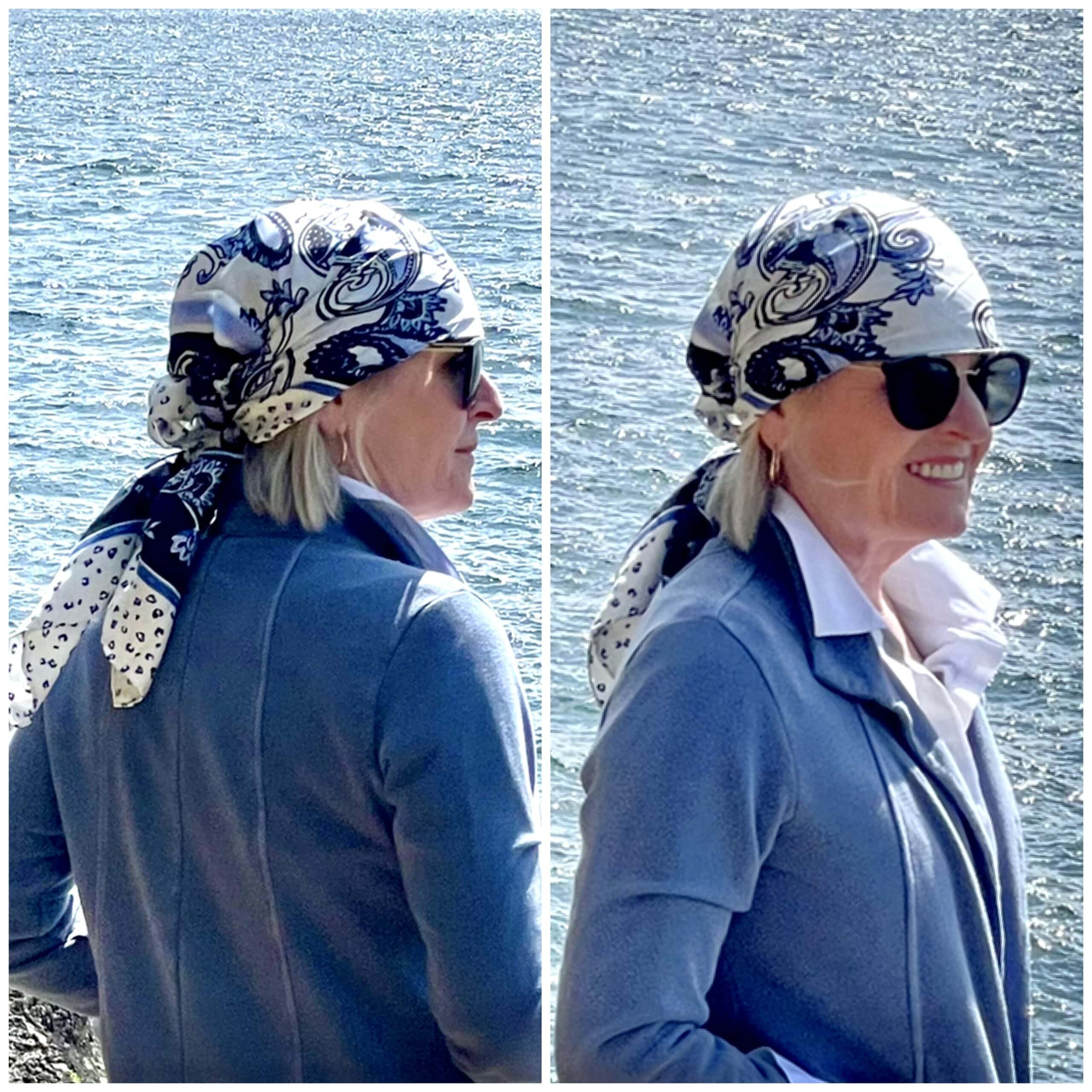 over 50 woman showing front and back of blue and white head scarf wrap while standing on the coastline