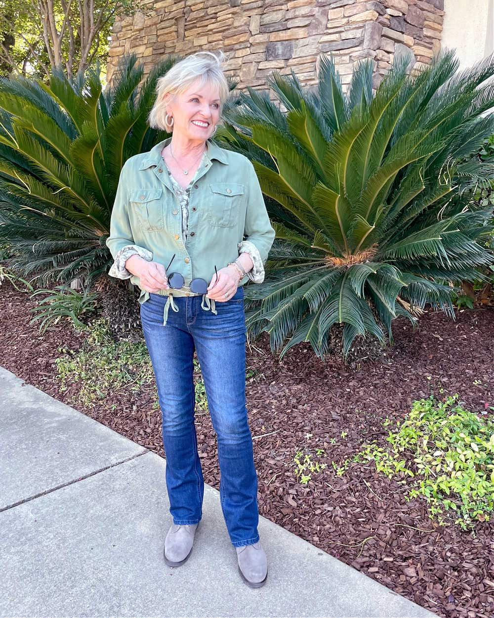 woman walking lightweight fall outfit of green jacket and jeans