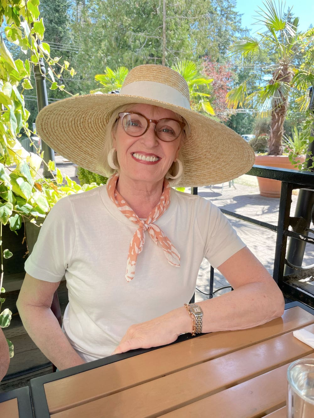 midlife blogger wearing large sunhat, tee and showing a summer scarf tied at her neck