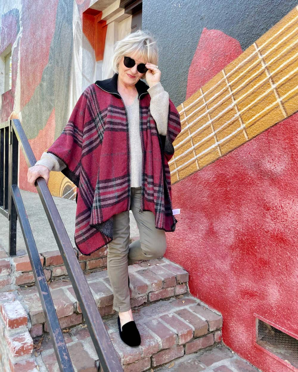 blonde woman walking down stairs in red plaid cape