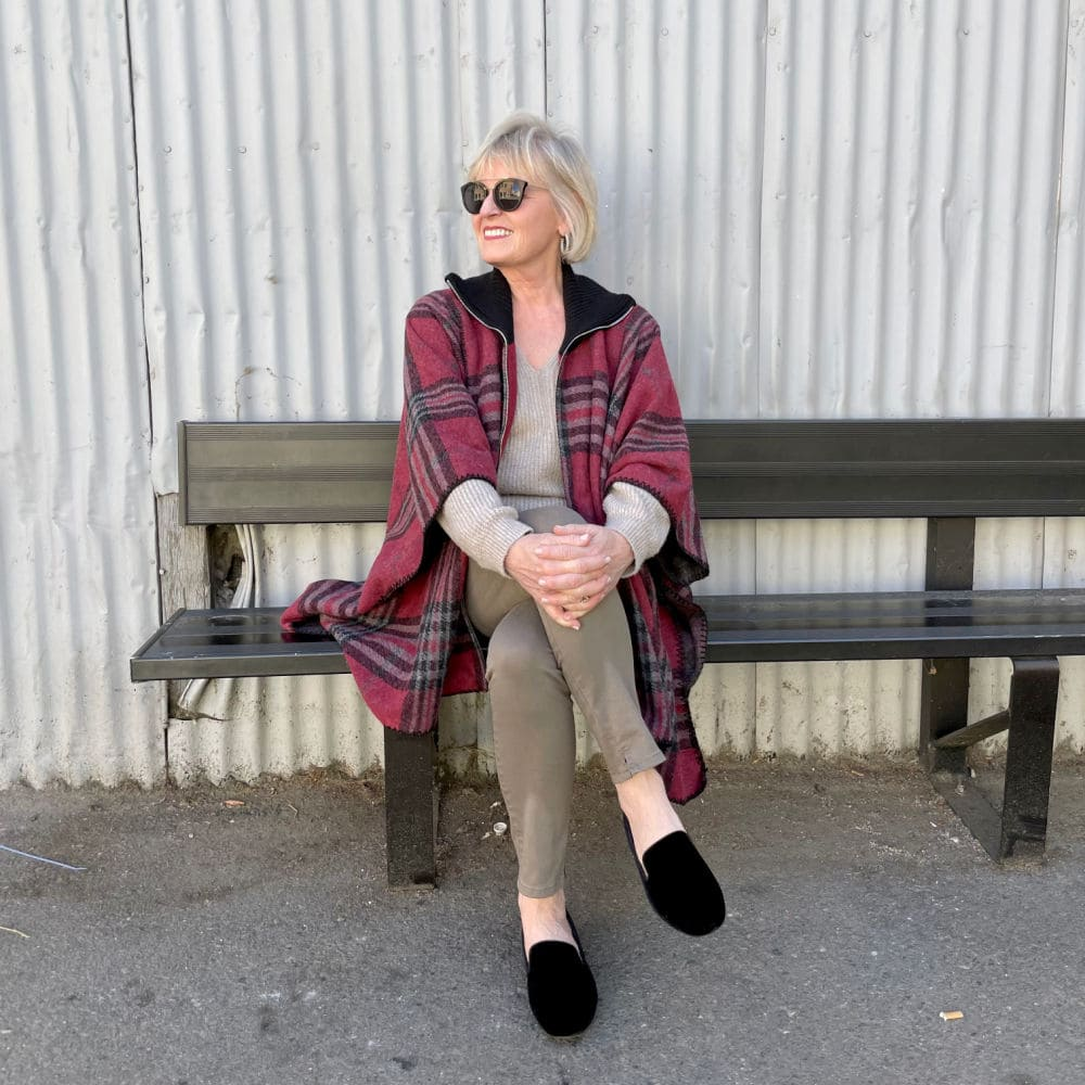 woman sitting on bench wearing red plaid cape