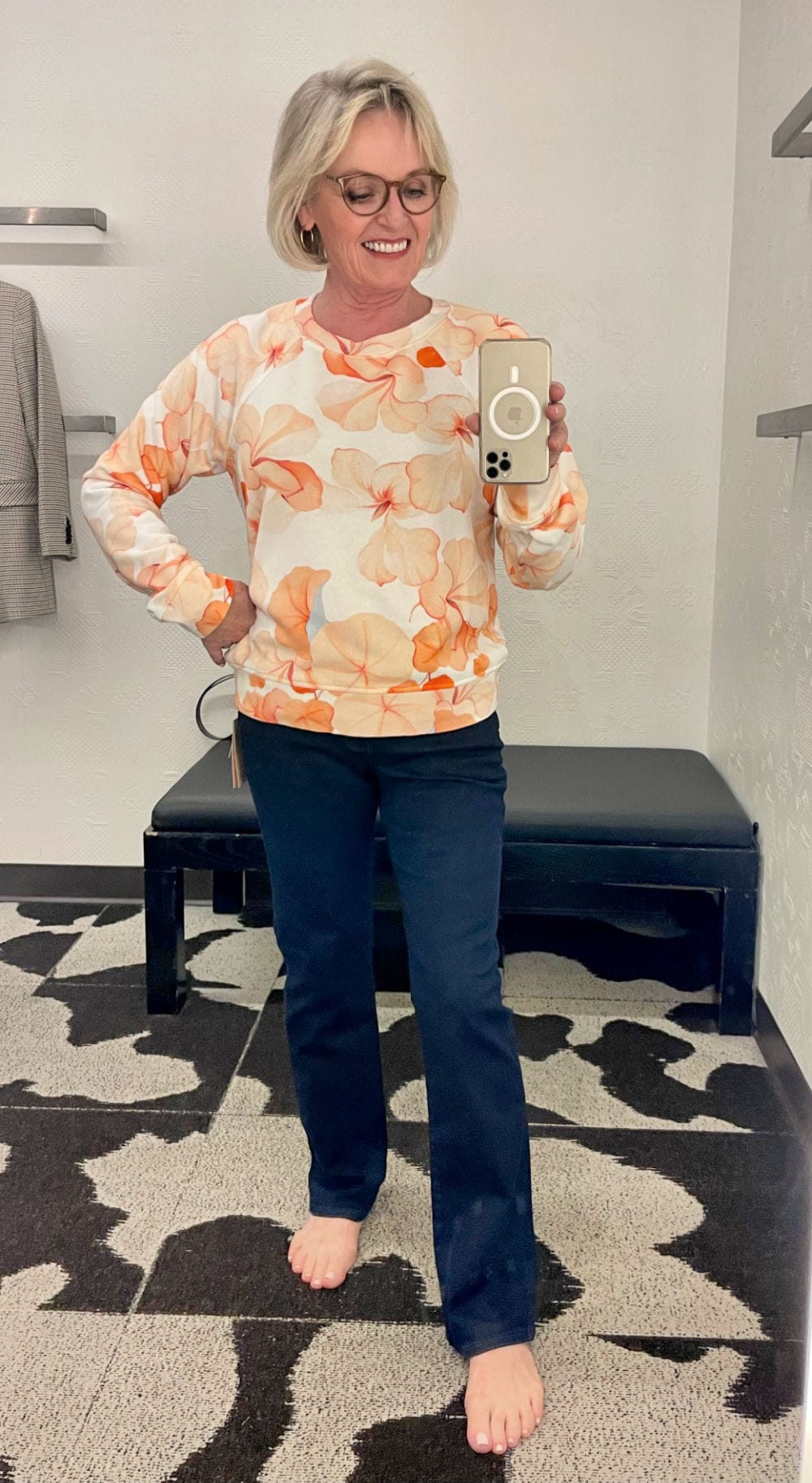 straight jeans and colorful sweatershirt on over 50 blogger in dressing room selfie