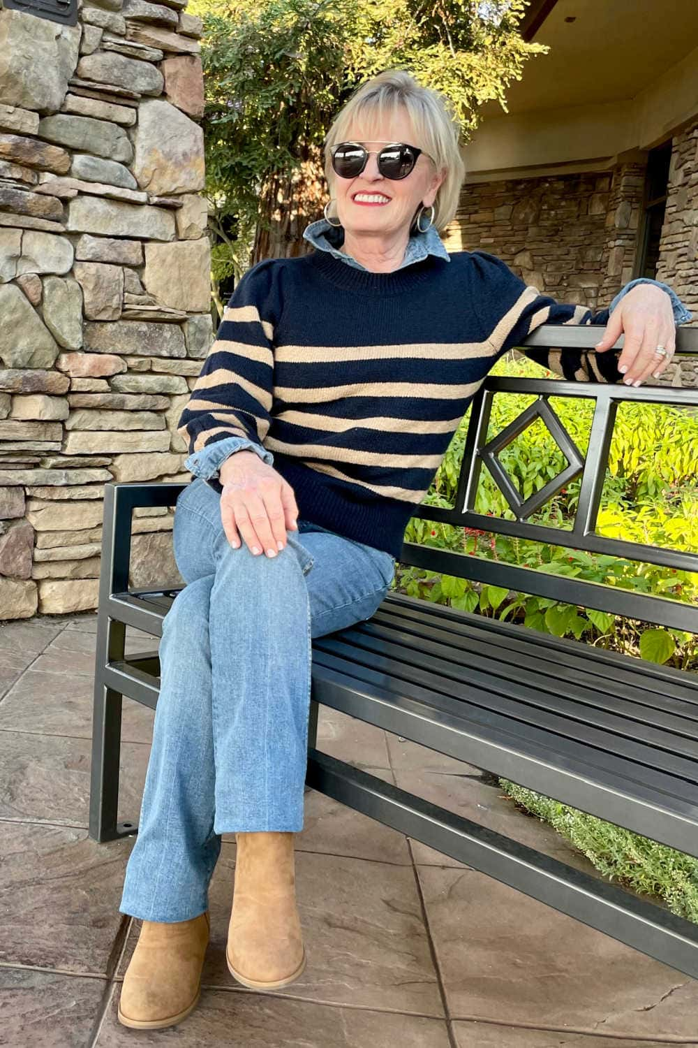 ench wearing camel suede booties, bootcut jeans and navy stripe pullover woman sitting on b