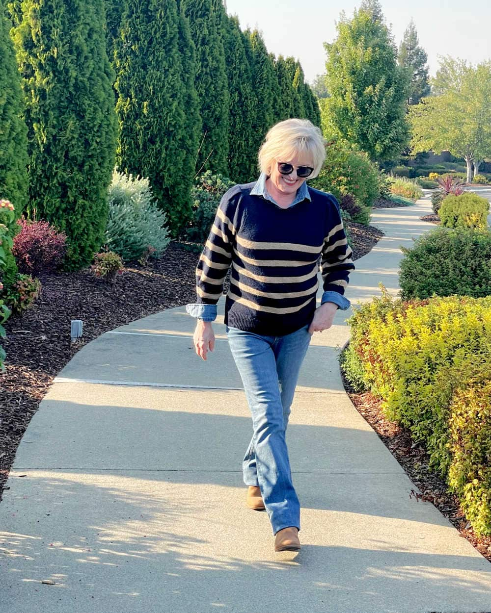 woman walking wearing striped free assembly sweater denim shirt and jeans