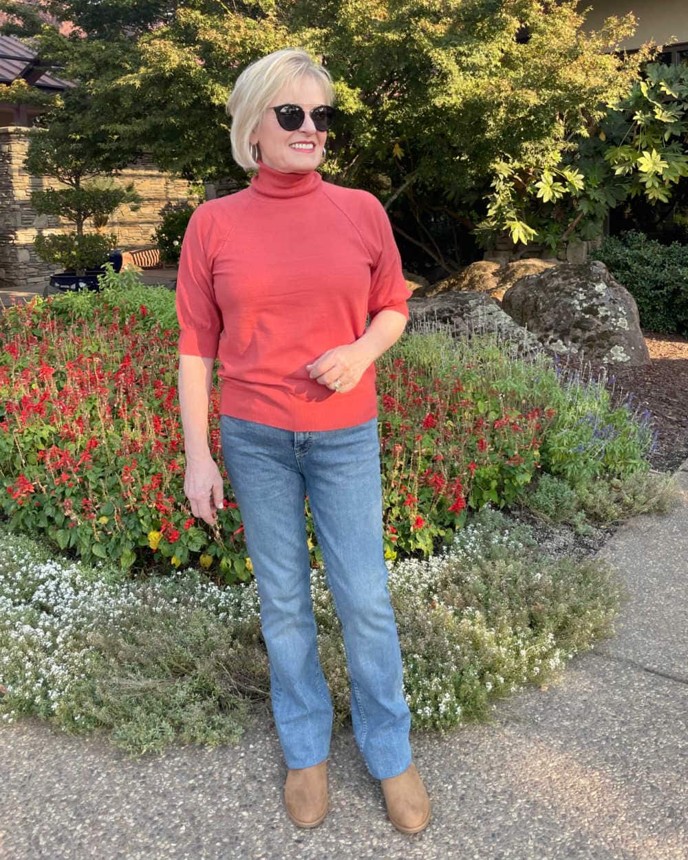 blond woman wearing coral sweater and blue jeans