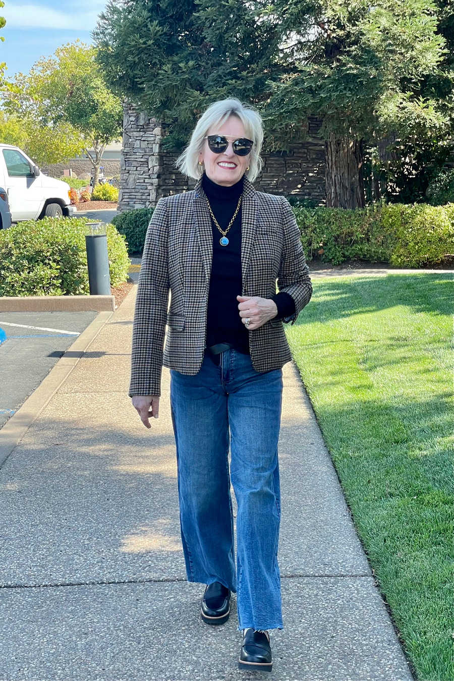 over 50 woman walking in wide legs jeans trend outfit