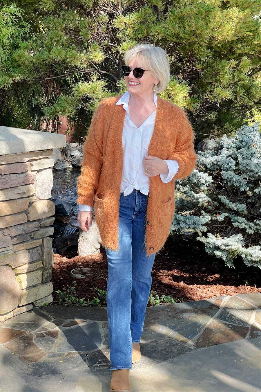 orange cardigamn with blue jeans and chelsea boots on blonde woman