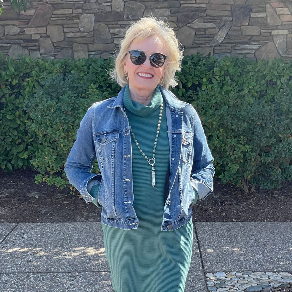 woman wearing denim jacket and teal dress with sunglasses