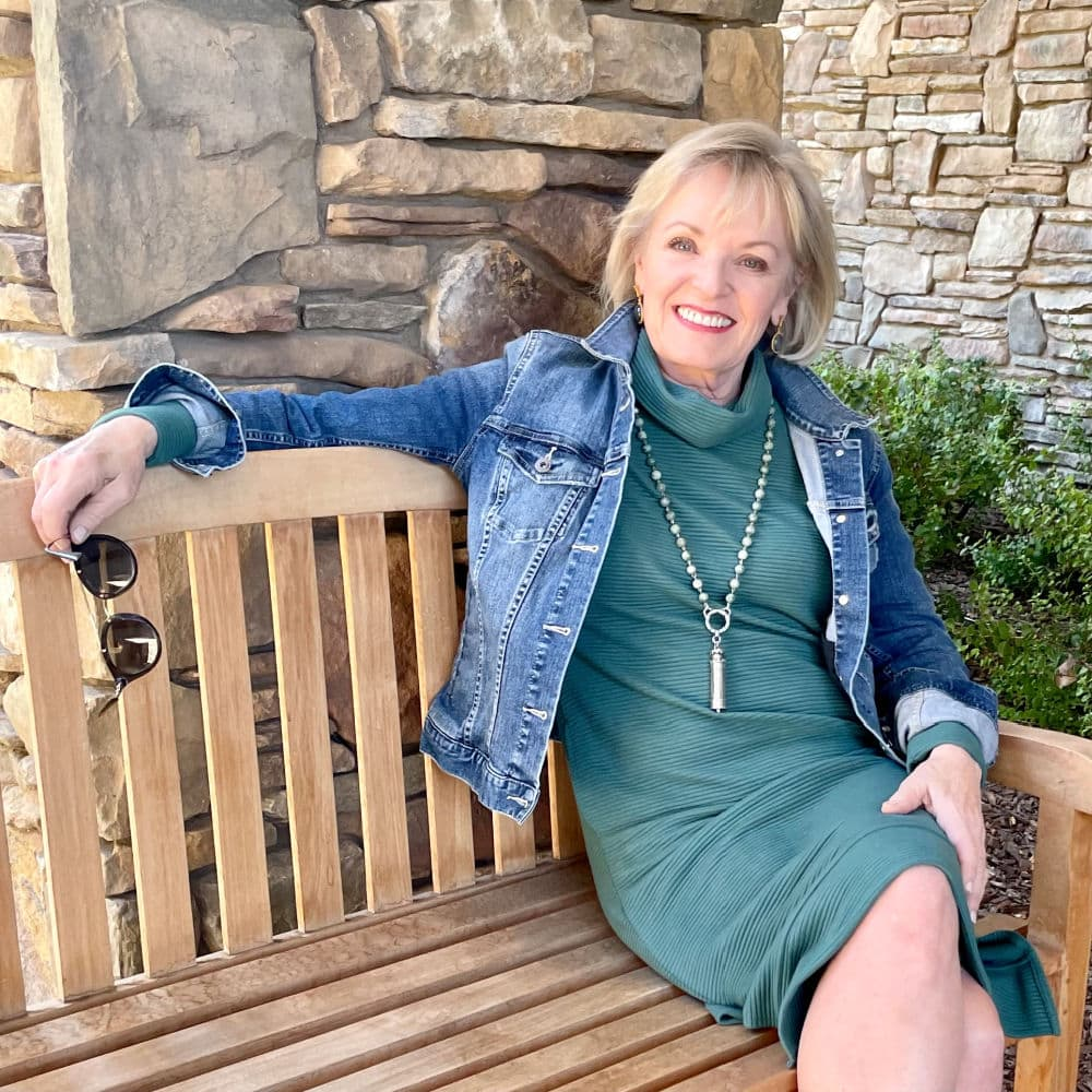 woman sitting on bench smiling into camera