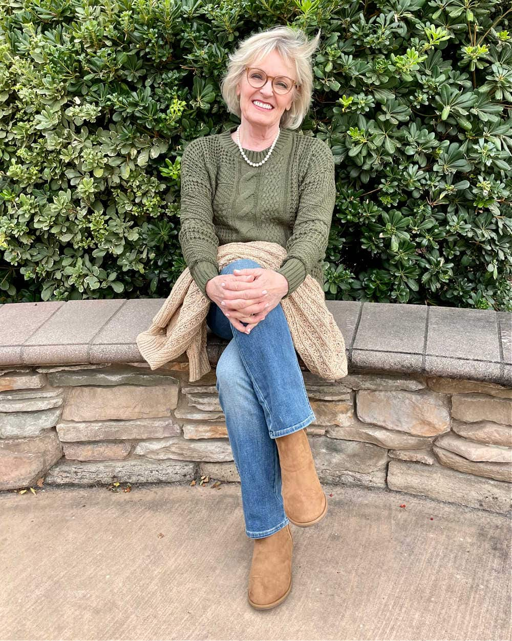blonde woman sitting on wall wearing green cable sweater and blue jeans from Walmart