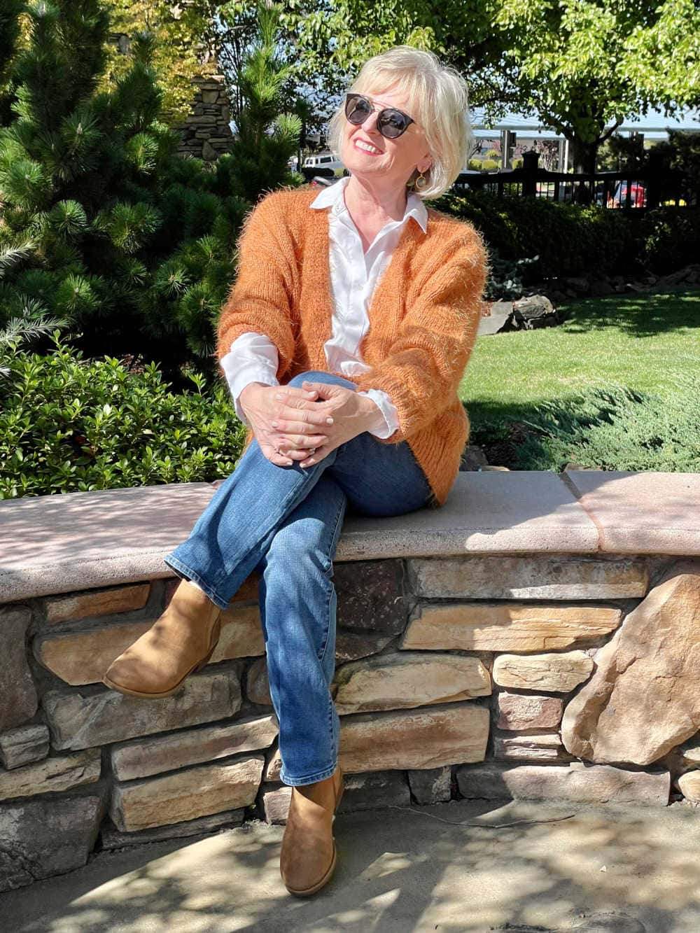 bolnd woman sitting on wall wearing rust colored cardigan and blue jeans
