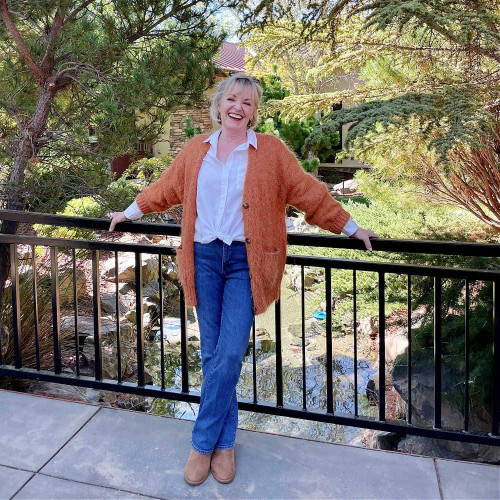 woman standing near railing wearing fall outfit