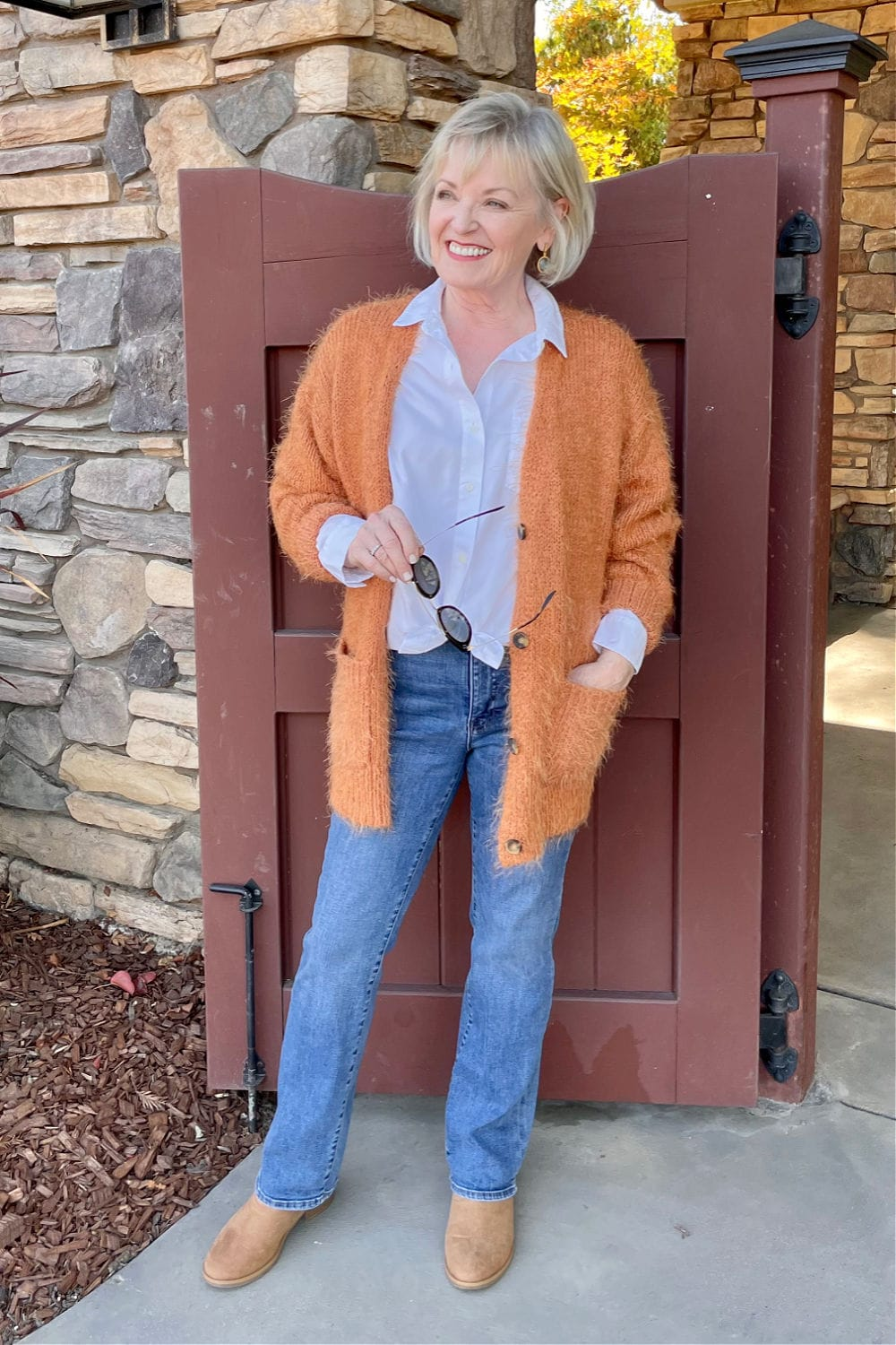 jennifer connolly of a well styled life wearing rust sweater and blue jeans