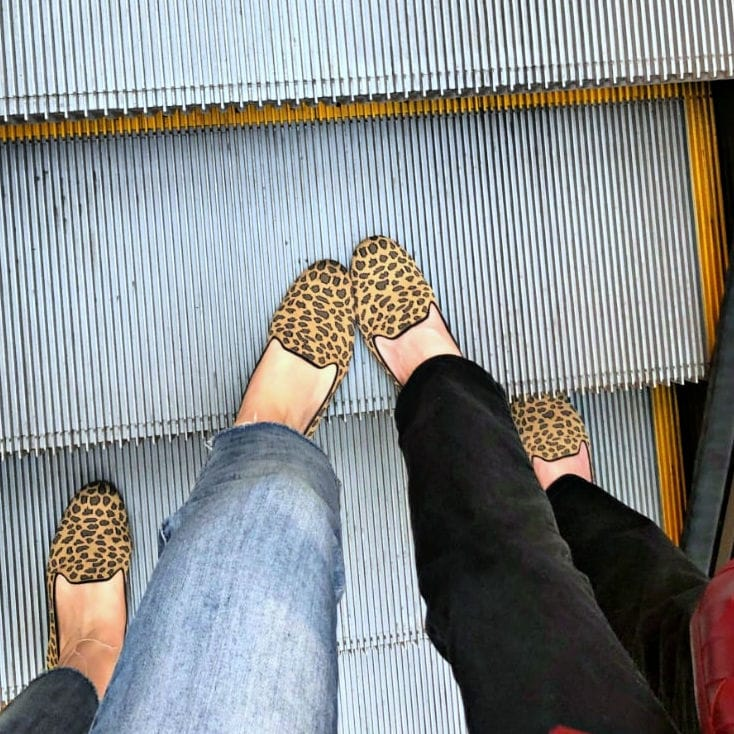 two pair of rothy's aniumal print loafers on escalator